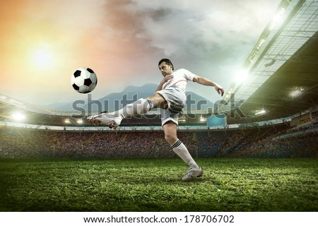 Soccer player with ball in action at stadium.