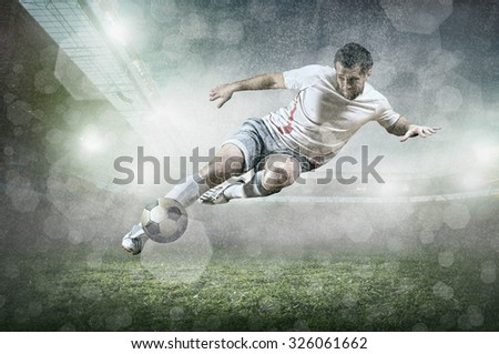 Soccer player with ball in action at stadium under rain. - stock photo