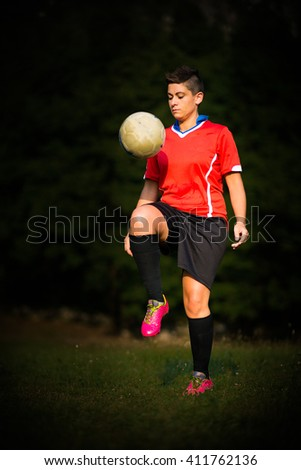 Soccer player woman dribbling alone in the meadow - stock photo