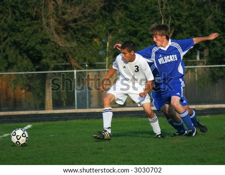 Soccer players fight for the ball - stock photo