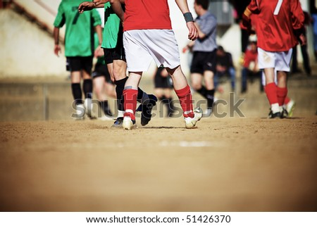 Soccer players running and playing a game on a sand field - stock photo