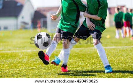 Soccer players running with ball. Children playing soccer in organized youth game. Young boys child in sportswear training soccer on a sports field. - stock photo