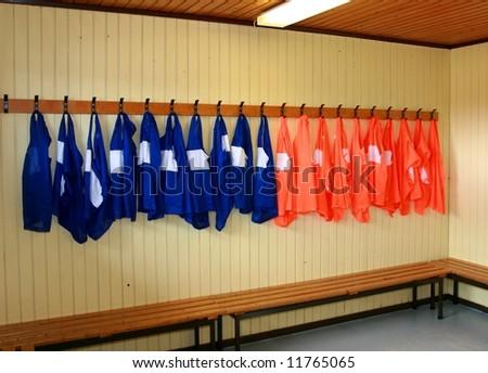Soccer practice vests hanging in a locker room - stock photo