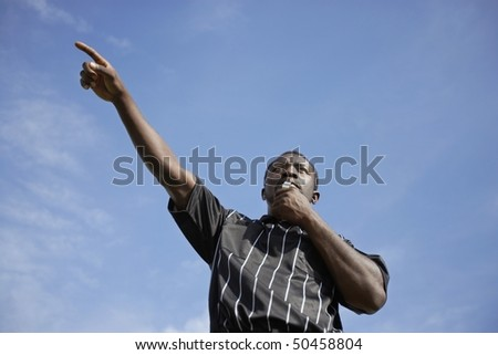 Soccer referee blowing whistle and pointing, portrait, low angle view