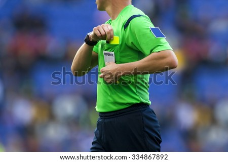 Soccer referee to point out a yellow card to a player during a match - stock photo