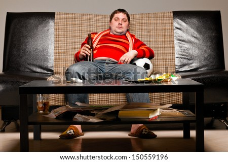 soccer supporter is sitting on sofa in red jersey - stock photo