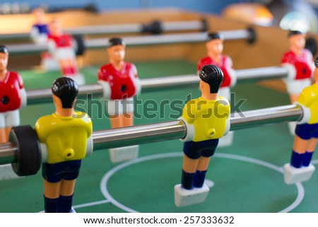 Soccer table game with yellow and red players - stock photo