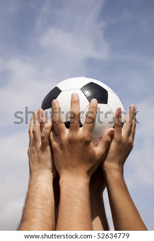 Soccer team raising a ball to the sky - stock photo