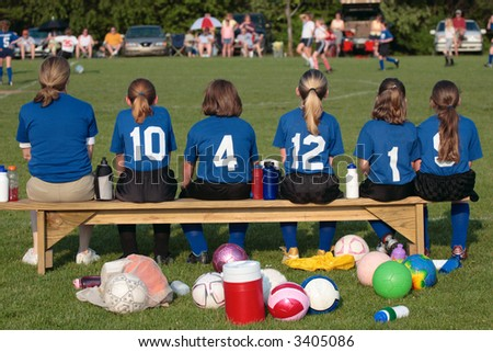 Soccer Team with Coach on sidelines on bench at Game. - stock photo