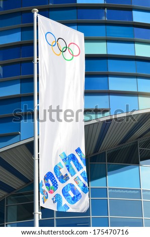 SOCHI, RUSSIA - FEBRUARY 7, 2014: Olympic flag with the symbol of the Sochi 2014 in front of the Ice rink for figure skating Iceberg in Olympic park  - stock photo