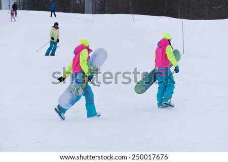SOCHI, RUSSIA - FEBRUARY 26, 2014: Two girls go with snowboards in hand at the ski resort. - stock photo