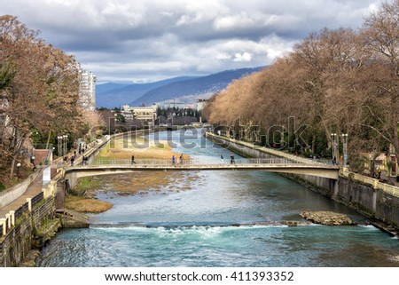 Sochi, Russia - February 8, 2016: View of river Sochi and peaks of the Main Caucasian ridge from Riviera bridge - stock photo