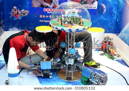 SOCHI, RUSSIA - November 21, 2014: Children make a robot at the robot Olympiad in Sochi . Here there was the World Robotic Olympiad 2014. It was attended by delegates from 47 countries. - stock photo