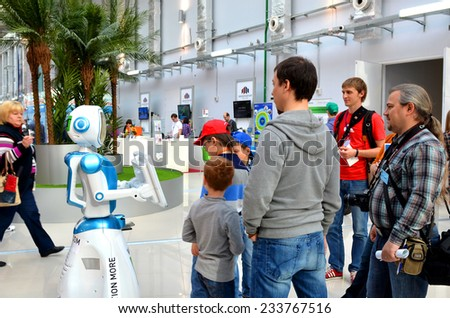 SOCHI, RUSSIA - November 21, 2014: People  People communicate with the robot in Sochi. Here there was the World Robotic Olympiad 2014. It was attended by delegates from 47 countries. - stock photo