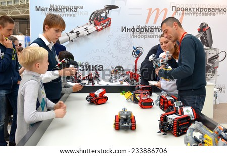 SOCHI, RUSSIA - November 21, 2014: The man explains the principle of operation of the robot for teenagers on World Robot Olympiad Russia 2014. It was attended by delegates from 47 countries - stock photo