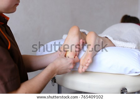 Sociable and professional man doctor actively rubs feet and conducts medical procedure, talking with female patient who lies on couch in light cosmetic salon. Man of European appearance with short