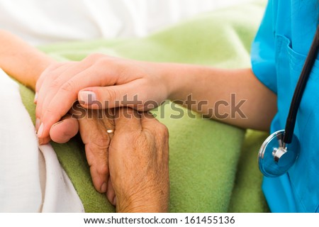 Social care provider holding senior hands in caring attitude - helping elderly people. - stock photo