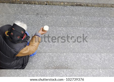 Social issues, old homeless woman begs on underground steps. With copyspace. - stock photo