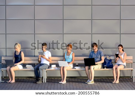 Social media addiction college students using laptop sitting in row - stock photo