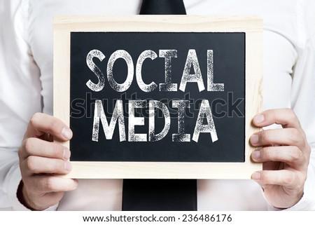 Social media background . Idea. Businessman holding board on the background with social media words - stock photo