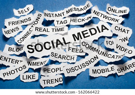 Social media concept torn newspaper headlines on blue background - stock photo