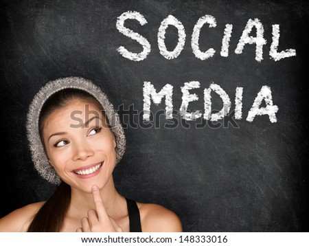 Social media concept with university student looking thinking at SOCIAL MEDIA text on blackboard. Female college student girl in front of black chalkboard. Trendy cool multiracial asian caucasian girl - stock photo