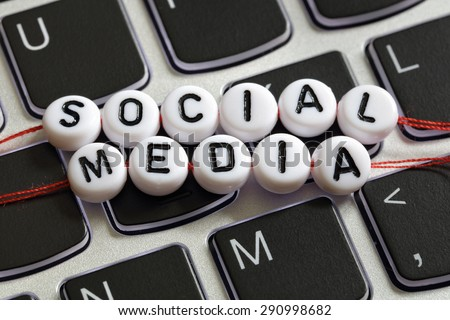 Social media letter beads on laptop keyboard keyboard concept for social networking, blogging, marketing and youth culture - stock photo