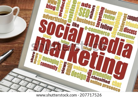 social media marketing word cloud on a laptop with cup of coffee - stock photo