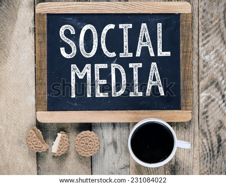 Social Media sign on blackboard with cup of coffee and biscuits on wooden background - stock photo
