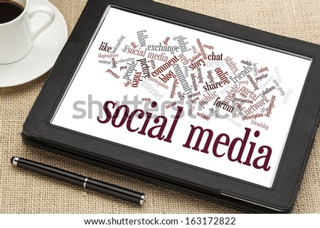 social media word cloud  on a digital tablet with a cup of coffee - stock photo