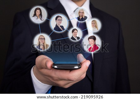 social network concept - modern smart phone in business man hand and icons with people portraits - stock photo