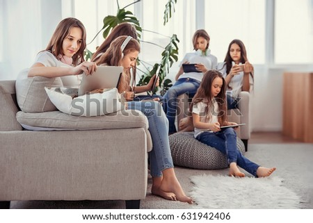 Social networks, friendship, technology and children concept. Group of teenage girls is using gadgets. Kids with phones and tablets, with smartphones and headphones