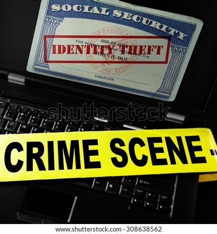 Social Security card with Identity Theft stamp on laptop screen with crime scene tape  - stock photo