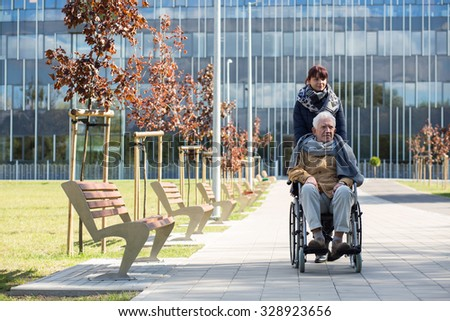Social worker and disabled man on a walk - stock photo