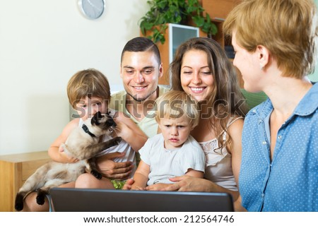 Social worker with laptop in hand, talking with young parents - stock photo