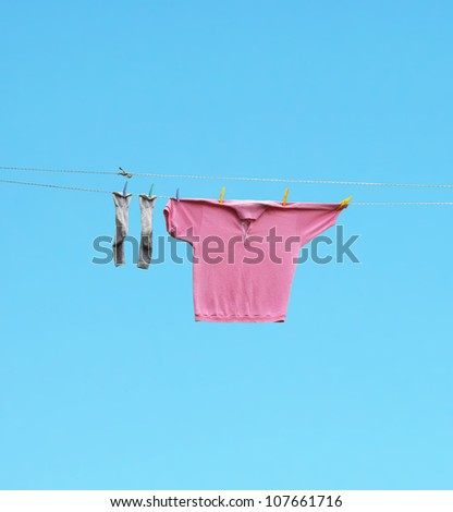 Socks and a pink shirt hang out to dry with blue light sky on the background