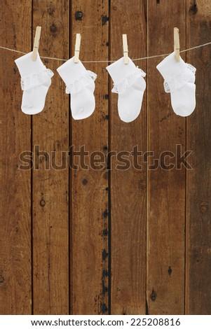 Socks on washing line against wooden background - stock photo