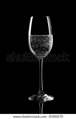 Soda on champagne glass, black background
