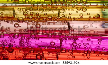 Soda water bubbles rising in a color glass of clean water. Macro close-up shot.  - stock photo