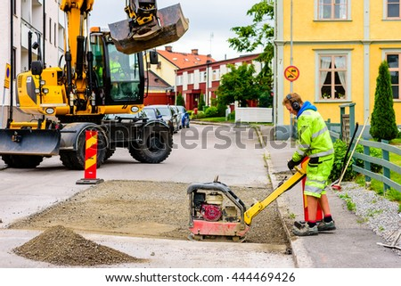 Soderkoping, Sweden - June 20, 2016: Young adult male person working a Honda GX200 reversible plate compactor on a roadwork site. Excavator in background.