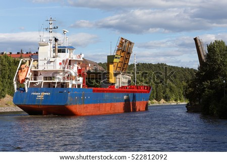 Sodertalje, Sweden - July 16, 2013: The cargo vessel Frisian Summer passes by the opened bridge Malarbron in Sodertalje Canal towards the Baltic Sea.
