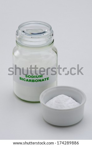 Sodium bicarbonate in a glass jar. White background.