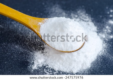 Sodium bicarbonate in a wooden spoon - stock photo