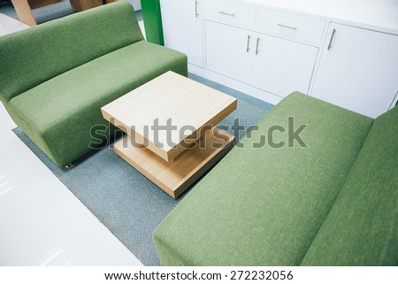 sofa and table at a small informal space in an office. - stock photo