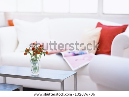 sofa and vase with flowers - stock photo