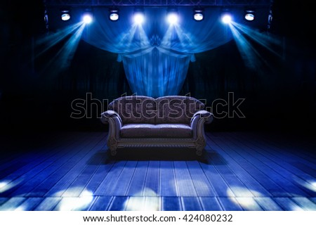 Sofa in dark room with stage light on it. Club light - stock photo