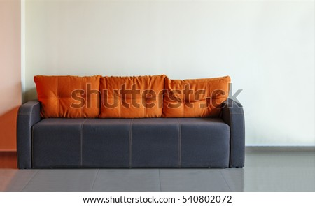 Sofa, interior design, office. Empty waiting room with a modern blue sofa with yellow cushions in front of the door and a clock on the wall