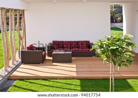sofa on modern wooden terrace with garden - stock photo