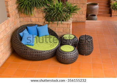 sofa weave Rattan stick chair with blue pillows on orange tile and old  brick wall. Wicker Furniture Stock Images  Royalty Free Images   Vectors
