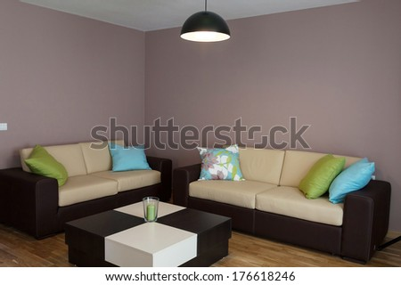 Sofa with three pillows and table - stock photo